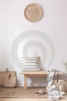 Pillow and blanket on wooden stool in white living room interior with brown plate. Real photo
