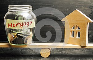 Miniature house and glass jar with coins on the scales. The inscription `mortgage`. credit for property / apartment. Business loan