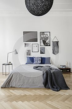 Bedroom with king size bed with blue pillows, grey duvet and blanket, gallery of framed artwork on the wall