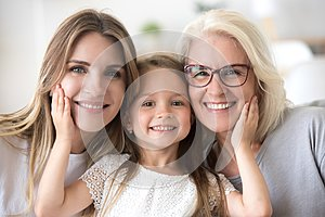 Portrait of girl hugging mom and grandmother making family pictu