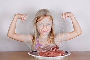 Carnivore keto diet concept - little blond girl eating raw meat