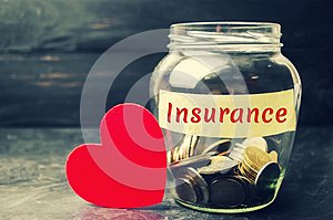Glass jar with coins and the inscription `Insurance`. The concept of medical insurance of life, family, health. Healthcare. Red he