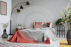 Patterned pillow and grey blanket on king size bed with dark orange duvet in luxury bedroom interior in elegant apartment