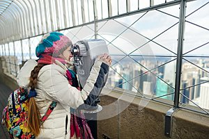 Happy young woman tourist at the observation deck of Empire State Building in New York City. Female traveler enjoying the view of