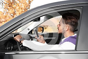 Young man using phone in driver`s seat