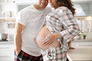 Pregnant woman with her husband in kitchen
