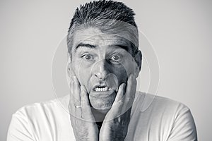 Portrait of a 40s 50s man in shock with a scared expression on his face making frightened gestures in human emotions feelings and