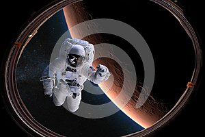 Astronaut in outer space from porthole on background of the Mars. Elements of this image furnished by NASA