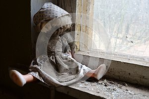 Doll on windowsill in abandoned kindergarten in destroyed village of Kopachi Chernobyl NPP alienation zone, Ukraine