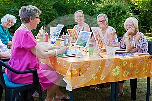 Happy group of senior ladies enjoying art class seated around a table outdoors in the garden painting with water colors while