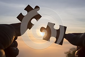 Silhouette of hand holding Jigsaw with Sunrise background. . symbol of association and connection. business strategy
