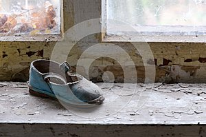 Children`s shoes on windowsill in abandoned kindergarten in destroyed village of Kopachi Chernobyl NPP alienation zone