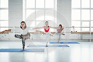 Group of young slim woman practice yoga exercise indoor class. People doing fitness together. Healthy lifestyle