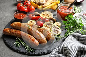 Slate plate with delicious sausages and vegetables served for barbecue party