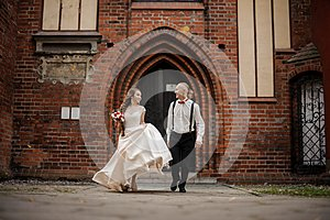 Young and happy married couple walking in a yard of old vintage red brick building