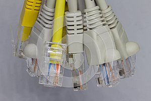 Yellow and gray ethernet rj45 cables on gray background