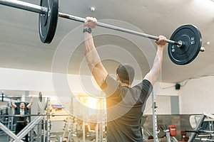 Muscular young man working with barbell heavy weights in training gym. Sport, bodybuilding, athlete, weightlifting, workout