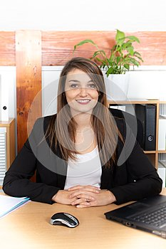 Attractive pretty young businesswoman sitting in front of laptop managing business
