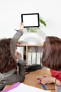 Businesswomen in office looking at blank white tablet to slide text or logo mark