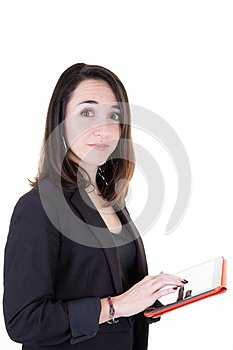 Portrait of young brunette businesswoman standing with tablet in white wall background
