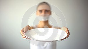 Skinny woman with taped mouth showing empty plate, concept of fasting, hunger