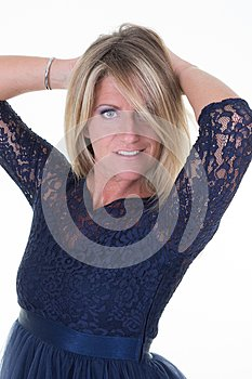 Pretty blonde middle aged woman posing in blue fashion dress on white background