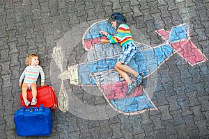 Two little children, kid boy and toddler girl having fun with with airplane picture drawing with colorful chalks on
