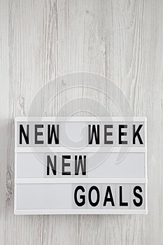 Modern board with text `New week new goals` over white wooden surface, top view. From above, flat lay, overhead. Copy space