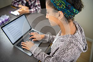 High school student girl learning online and doing homework using a laptop computer