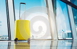 Isolate traveler tourist yellow suitcase at floor airport on background large window sun flare, bright luggage waiting in departur