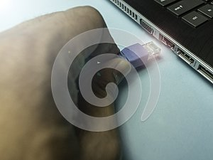 Hand plugging in the internet cable to a laptop