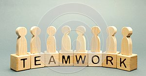 Wooden blocks with the word Teamwork and business team of employees. The concept of cooperation. Constructive feedback. Joint