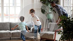 Excited black dad playing funny game with children at home