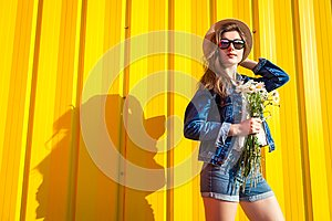 Portrait of hipster girl wearing glasses and hat with flowers against yellow background. Summer outfit. Fashion. Space