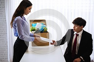 Business woman sending letter for resignation to boss with cardboard box in desk at office. Concept resign depress and resignation
