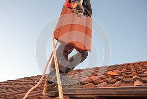 Worker carrying roof tile at the rooftop