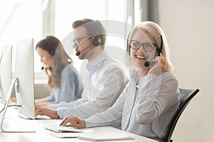 Happy mature female call center agent looking at camera smiling