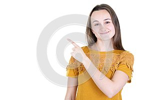Attractive young woman wearing mustard shirt posing pointing with finger