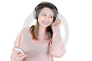 Portrait of cheerful cute young woman listening music in headphones isolated on white background Using phone