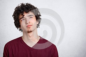 Portrait of thinking young man with dark curly hair, stands with thoughtful facial expression, dresses maroon shirt. Student