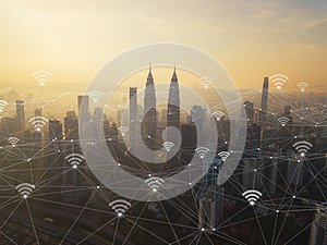 Digital network connection lines and wifi icons with Kuala Lumpur Downtown, Malaysia. Financial district in smart city in