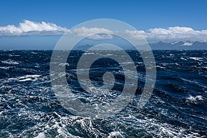 View of Atlantic Ocean and distant mountains, choppy water, calm blue sky with white clouds