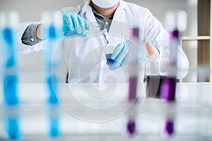 Biochemistry laboratory research, Scientist or medical in lab coat holding test tube with reagent with drop of color liquid over