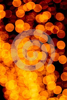 Unfocused abstract orange bokeh on black background. defocused and blurred many round light