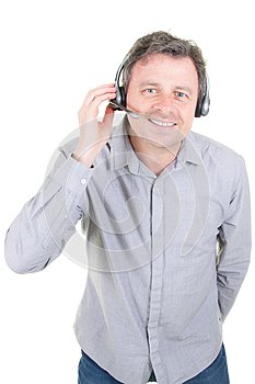 Smiling customer support phone operator man in call center in white background