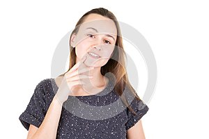 Young woman seductively holding finger to chin on white background