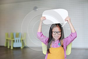 Adorable Asian little girl holding empty blank speech bubble to say something in the classroom with smiling and looking straight