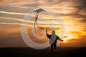 Flying a kite. The boy runs across the field with a kite. Silhouette of a child against the sky. Bright sunset