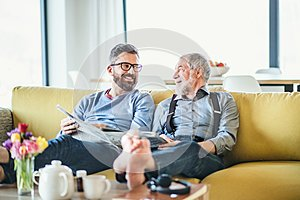 An adult hipster son and senior father sitting on sofa indoors at home, talking.