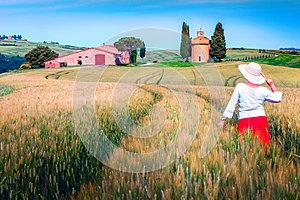 Cheerful woman enjoying the view in grain fields, Tuscany, Italy